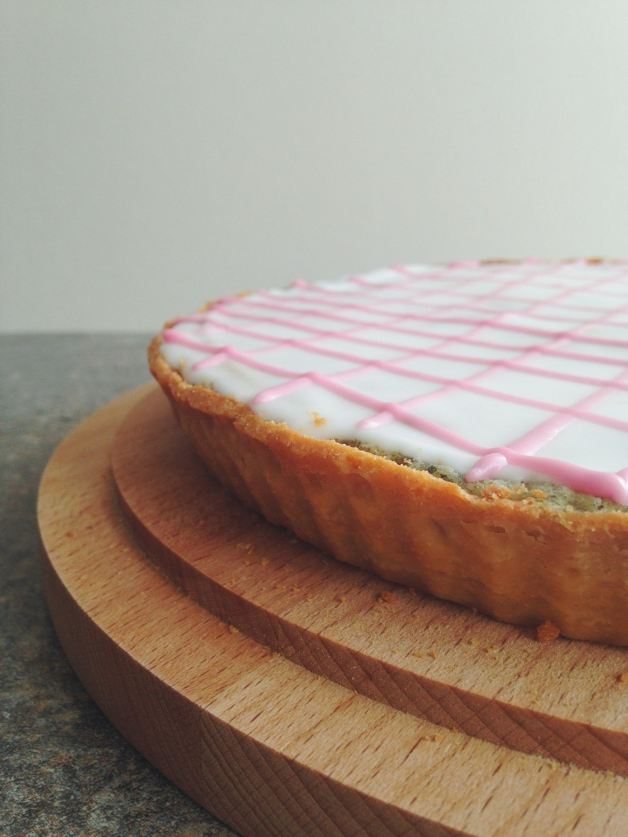 Side view of tart with pink pattern on white icing