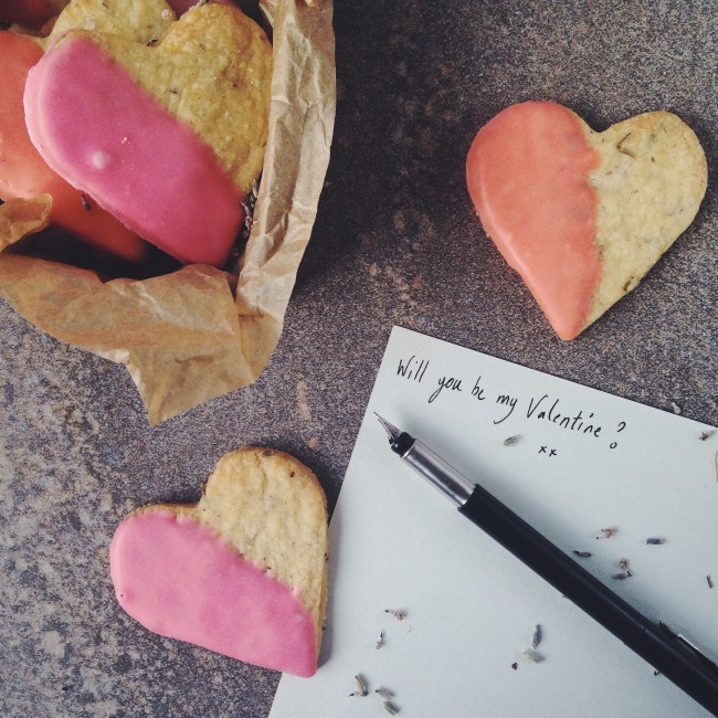 Scatter heart biscuits half dipped in pink pastel, with box of biscuits top left, and a letter reading 'Will you be my valentine?' in fancy type next to an open fountain pen bottom right