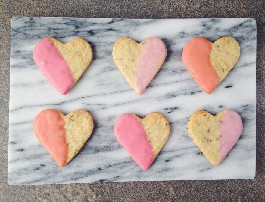 Six heart biscuit half dipped in pastel pinks in two rows on a marble background