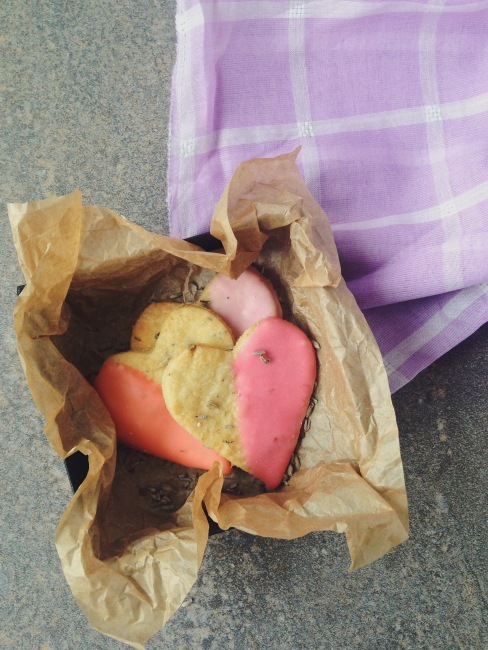 Three heart shaped biscuits half dipped in pastel pink in a small box to bottom left, with a purple gingham cloth top right