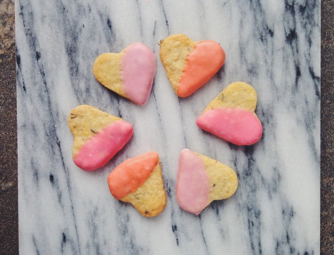 Six heart shaped biscuits half dipped in pastel pinks arranges with point facing in in a circle, on a marble background